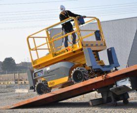 Представитель компании, загоняет подъемник на платформу автомобиля перевозчика, для дальнейшей транспортировки на новый объект.